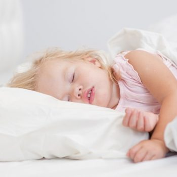 little baby girl sleeping on a bed.